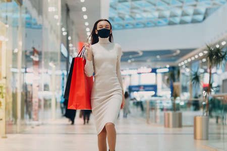 Young adult woman in protective medical face mask carrying paper shopping bags in hands at retail store