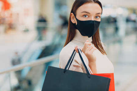 Young adult woman in protective medical face mask carrying paper shopping bags in hands at retail store mall Foto de archivo