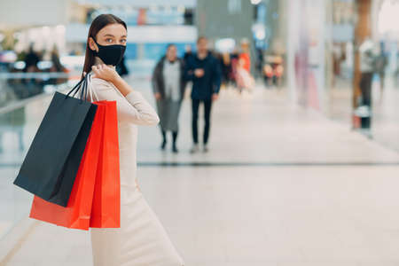 Young adult woman in protective medical face mask carrying paper shopping bags in hands at shopping mall