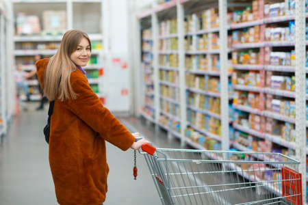 Woman with shopping cart at retail store shelves with food.