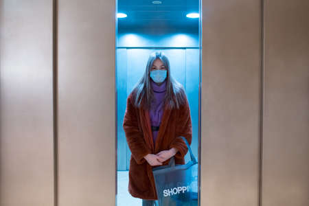 Young woman standing in closing elevator in medical face mask.
