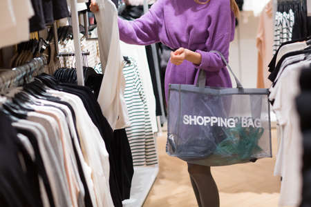 Young woman with shopping bag chooses clothes in store