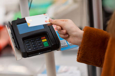 Woman hand with credit bank card pays for purchases at the checkout counter in the store. Contactless payment in new normal shopping,