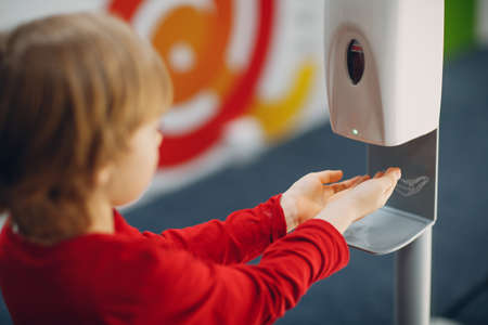 Child boy kid using automatic alcohol gel dispenser spraying on hands sanitizer machine antiseptic disinfectant, Foto de archivo