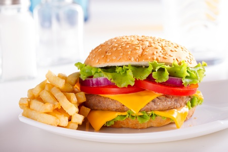 ファーストフードを食べる。ハンバーガーとフライド ポテト、皿の上。