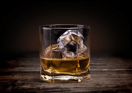 scotch: Glasses of whiskey on wood background.