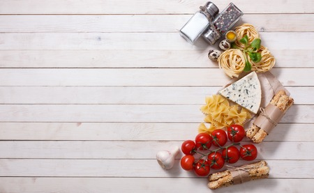 Overhead view of ingredients for an Italian pasta recipe on rustic wood boards with copyspace