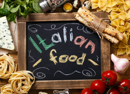 Italian food on vintage wood background, with chalkboard, with text