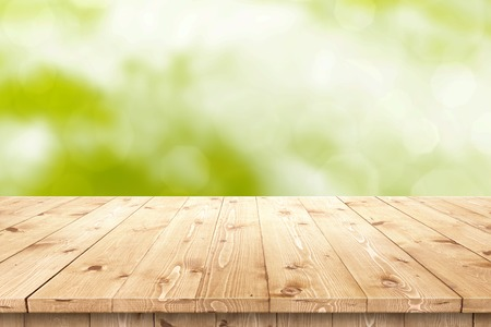 product placement: Empty wooden table in a sun drenched summer garden for product placement or montage with focus to the table top in the foreground, with summer bokeh background.