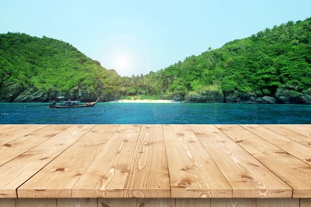 Empty wooden table in a sun drenched summer garden for product placement or montage with focus to the table top in the foreground, with summer background. Imagens