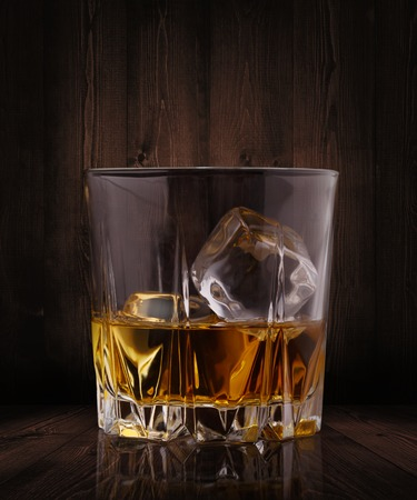 Glasses of whiskey with ice cubes on wood background Imagens