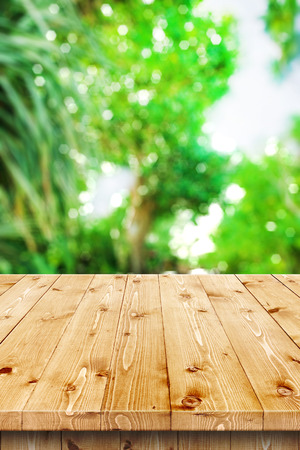 knotty: Empty wooden table in a sun drenched summer garden for product placement or montage with focus to the table top in the foreground, with summer bokeh background.