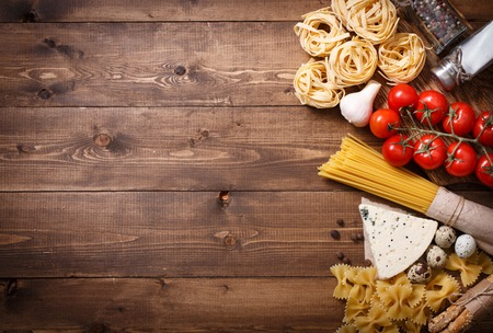 Overhead view of ingredients for an Italian pasta recipe on rustic wood background