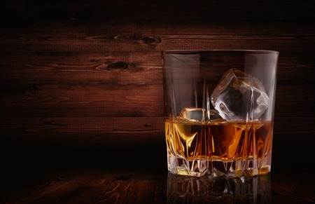 Glasses of whiskey with ice cubes on wood background Archivio Fotografico