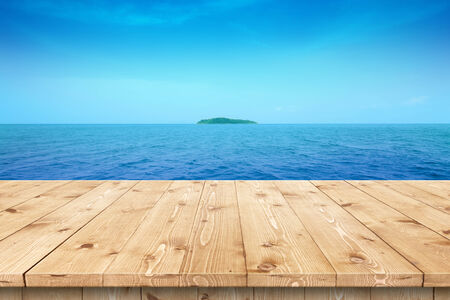 sun drenched: Empty wooden table in a sun drenched summer garden for product placement or montage with focus to the table top in the foreground, with summer background. Stock Photo