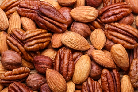 Background texture of assorted mixed nuts including cashew nuts, pecan nuts, almonds