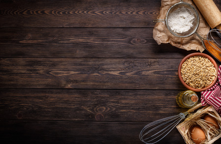 Ingredients for baking on empty dark wooden background with plac