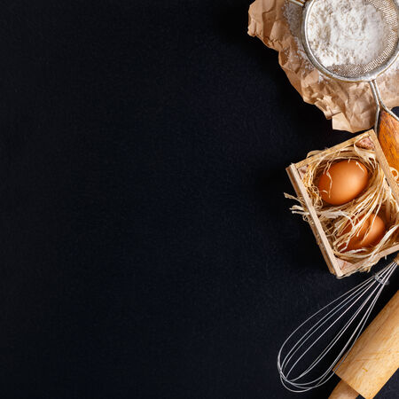 Ingredients for baking including eggs and flour, with sieve and