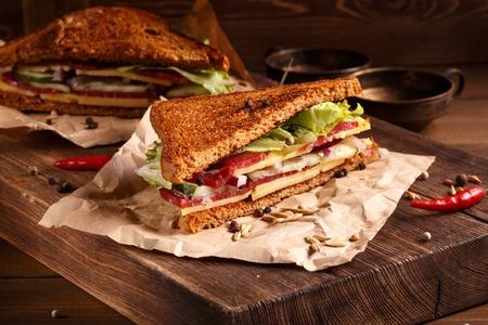 sandwich de pollo: Dos piezas de s�ndwich club en papper edad con tabla de cortar grande Foto de archivo
