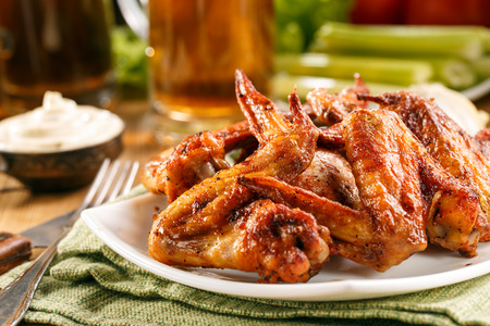 Roasted wings on the plate with sauce and beer on background, close-up.