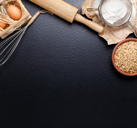 Ingredients for baking including eggs and flour, with sieve and whisk flour on empty light wooden background with place for text or recipes.