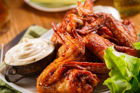 hot wings: Roasted wings on the plate with sauce close-up. Stock Photo