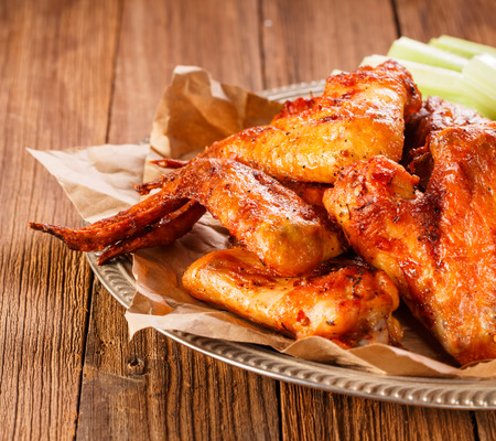 Roasted wings on wooden background