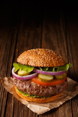 Classic Burger close up  on wooden background.