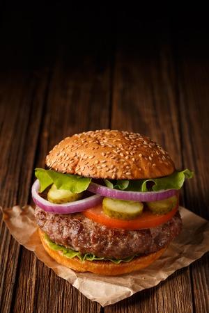 hamburguesa: Classic Burger cerca sobre fondo de madera. Foto de archivo
