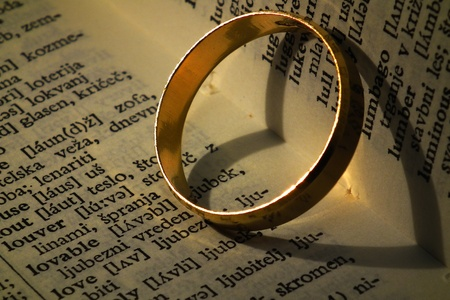 parejas enamoradas: Anillo de oro haciendo forma de coraz�n en el libro deja Foto de archivo