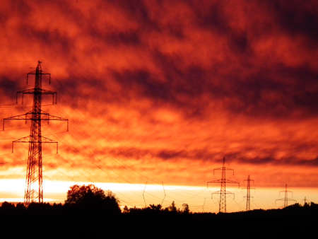 Line of power electric mast in early morning red dawn