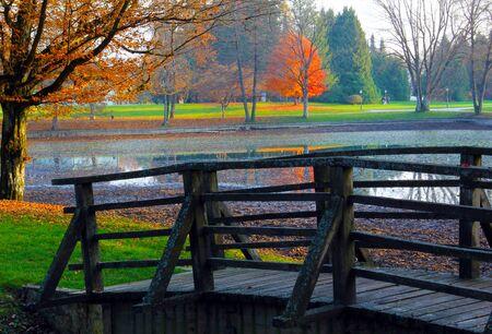 A wooden bridge in beautiful autumn colored park.