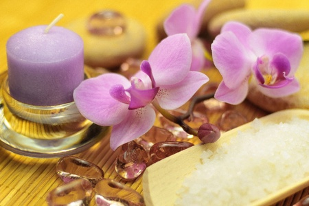 Purple candle and orchid, salt, rocks and stones for spa treatment. photo