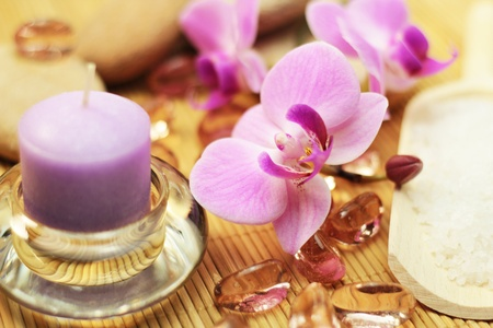 Wild orchid, purple candle, salt and rocks for spa treatment. photo