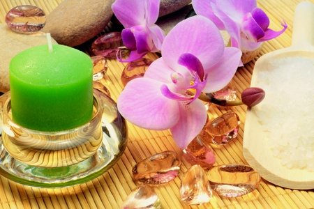 Green candle, purple orchid, salt and glass stones with rocks for spa treatment. photo