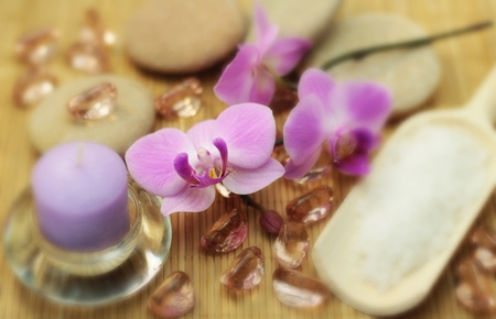 Red candle, purple orchid,  glass stones and real stones. A concept of spa. photo