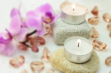 Weiße Kerzen, violetten Orchidee, Glassteinen und kleine Steine ??für Spa auf weißem Hintergrund.