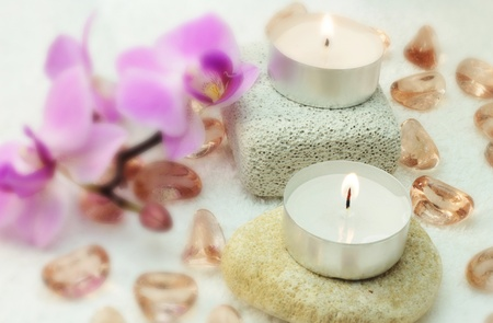 White candles, purple orchid, glass stones and small rocks for spa on white background.