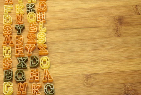 Pasta in shape of letters as background. Stock Photo