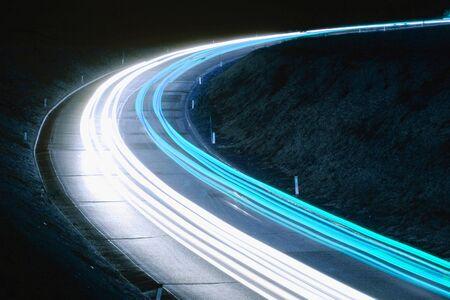 Modré stezky automobilů na silnici v noci