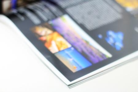 Open magazine on white table  Standard-Bild