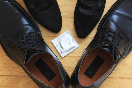 Concept of safe sex; man and woman shoes and a condom on the floor  Stock Photo - 12667402