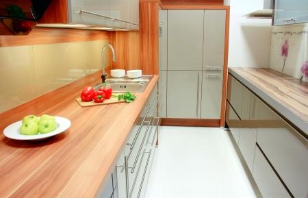 Nová kuchyňská linka interiér; zelené jablko, paprika a petržel v kuchyni Reklamní fotografie