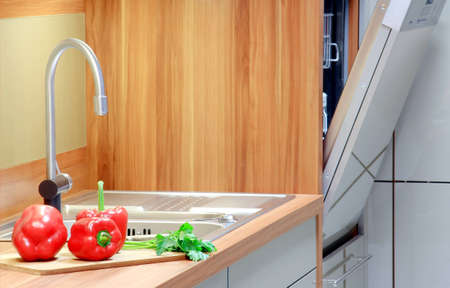 Open dishwasher, red pepper, green parsley in the kitchen Stock Photo - 13767798