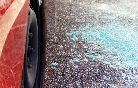 car theft: Vidrios rotos sobre el asfalto, cerca de un coche, los valores de robo stoled desde el coche