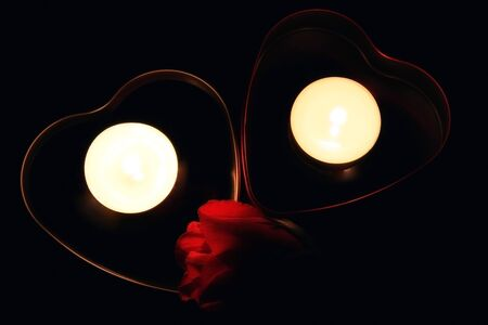 Two boxes in shape of heart with candle and red rose  photo