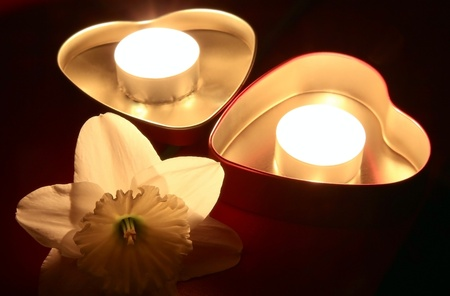 Two boxes in shape of hearts with candles and flower of Narcissuss  photo