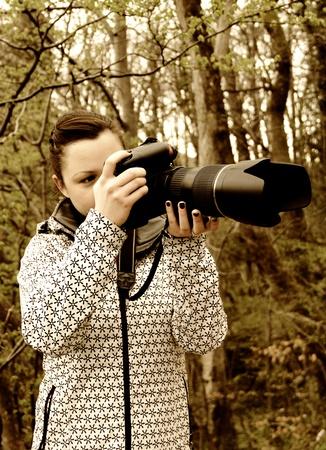 Mladá žena fotograf s dlouhým zoomem v přírodě