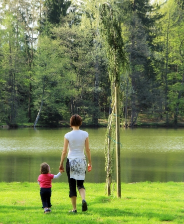 Mother is taking young child to the lake  Stock Photo