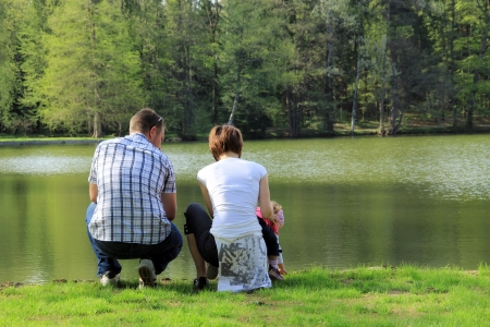 A family in the park, near the lake Stock Photo - 13612437